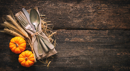 Autumn background from pumpkins and wheat with vintage place setting on old wooden table. Thanksgiving day concept Foto de archivo - 110353043