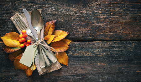 Autumn background from fallen leaves and fruits with vintage place setting on old wooden table. Thanksgiving day concept Foto de archivo - 110353045