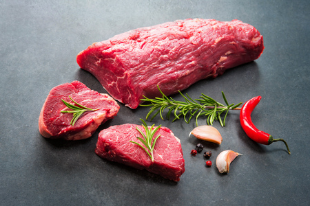 Fresh and raw beef meat. Whole piece of tenderloin with steaks and spices ready to cook on dark background 