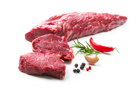 Fresh and raw beef meat. Whole piece of tenderloin with steaks and spices ready to cook isolated on white background Foto de archivo - 111188734
