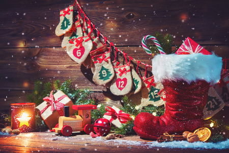 Christmas background. Advent calendar and Santa's shoe with gifts on rustic wooden background Foto de archivo - 111188735