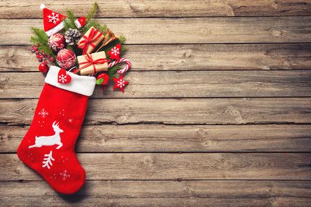 Weihnachtsstrumpf und Spielzeug über rustikalem Holzhintergrund Standard-Bild