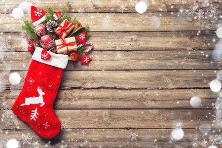 Weihnachtsstrumpf und Spielzeug über rustikalem Holzhintergrund