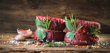 Raw beef fillet steaks mignon with spices on wooden background Foto de archivo - 111188740