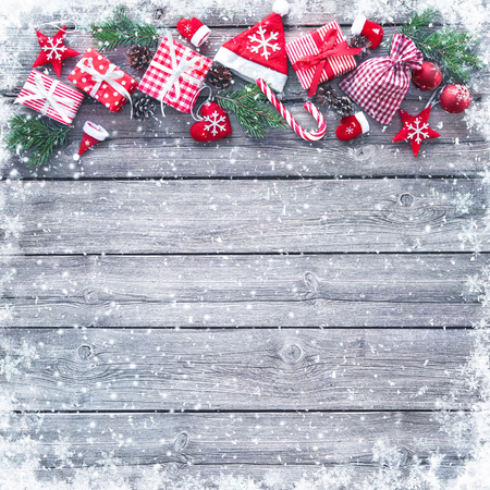 Christmas background with decorations and gift boxes on wooden board Foto de archivo - 111448515
