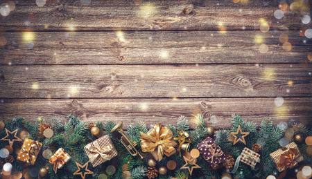 Christmas background with decorations and gift boxes on wooden board Foto de archivo - 111448516