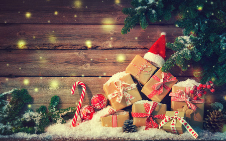 Christmas background with decorations and gift boxes on wooden board Foto de archivo - 111448494