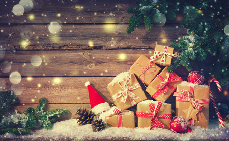 Christmas background with decorations and gift boxes on wooden board Foto de archivo - 111448496