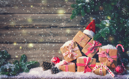 Christmas background with decorations and gift boxes on wooden board Foto de archivo - 111448497
