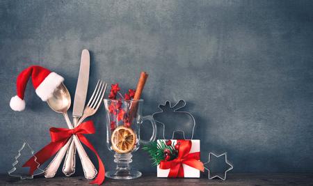 Rustikaler Hintergrund für Weihnachtsessen mit Besteck, Geschenkbox und Weihnachtsmütze