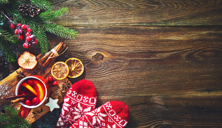 Christmas mulled red wine with spices and fruits on a wooden rustic table. Traditional hot drink at Christmas time Foto de archivo - 112560191