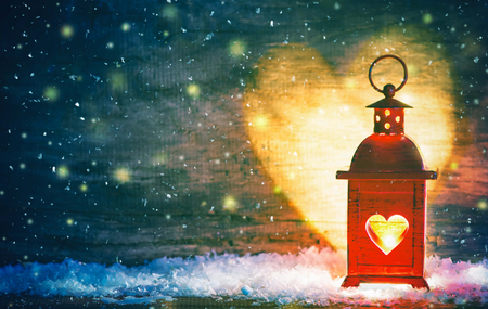 Romantic background or greeting card for Christmas or Valentines Day. Red lantern with a heart cut out lit by a glowing candle. Heart-shaped shadows on the wall Foto de archivo - 112560197