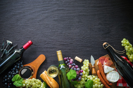 Wine bottles with grapes, cheese, ham and corks on dark background with copy space Foto de archivo - 112560199