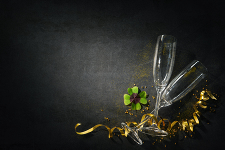 New Years Eve or Birthday celebration. Two champagne glasses with a shamrock as lucky charm on dark Stockfoto