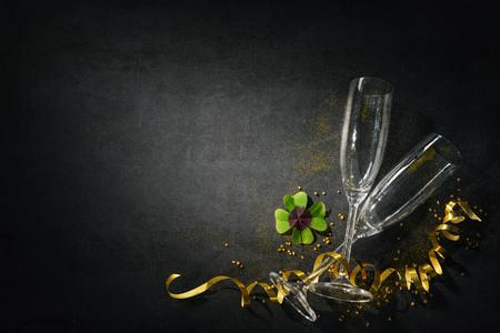 Oudejaarsavond of verjaardagsviering. Twee champagneglazen met een klavertje als geluksbrenger op donker