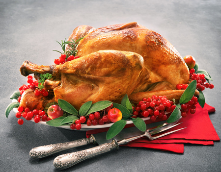 Christmas or Thanksgiving turkey garnished with red berries and sage leaves Stock Photo