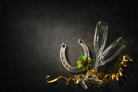 New Years Eve or Birthday celebration. Two champagne glasses with a horseshoe and shamrock as lucky charm on dark