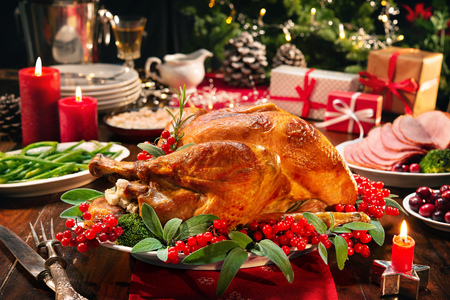 Christmas turkey dinner. Baked turkey garnished with red berries and sage leaves in front of Christmas tree and burning candles Imagens - 113928814