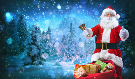 Santa Claus with a Christmas bell and a bag full of presents shows thumbs up