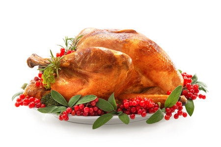 Dinde de Noël ou de Thanksgiving garnie de baies rouges et de feuilles de sauge isolées sur blanc Banque d'images