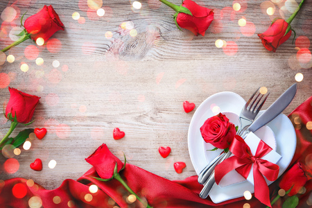 Plates in shape of heart, holidays table setting with a gift box on wooden table. Valentines day concept Фото со стока