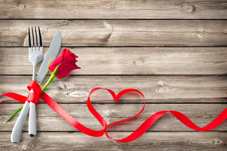 Silverware tied up with red ribbon in heart shape on wooden planks.