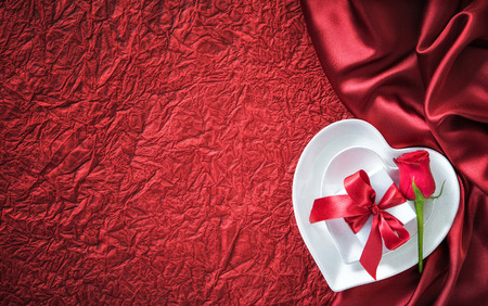 Plates in shape of heart, holidays table setting with a gift box on red