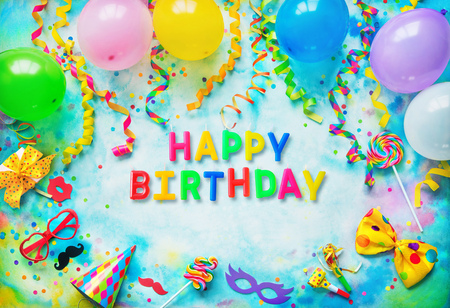 Balloons, gift box, confetti, candy, bow tie, sunglasses, party hat and streamers on colorful  with text Happy Birthday from birthday candles. Top view
