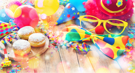 Colorful carnival or party background with donuts, balloons, streamers and confetti and funny face formed from wig, nose and glasses on rustic wooden planks with copy space Stock fotó