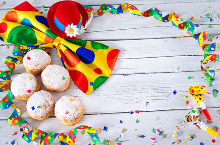Krapfen, berliner or donuts with bow tie, party hat, streamers and confetti on white wooden planks. Colorful carnival or birthday background