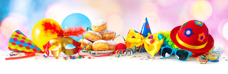 Colorful carnival or party background with donuts, balloons, streamers and confetti and funny face formed from wig, hat and eyeglasses