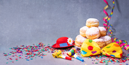 Krapfen, berliner or donuts with bow tie, party hat, streamers and confetti. Colorful carnival or birthday background Imagens