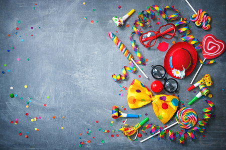 Colorful carnival or party background streamers and confetti and funny faces formed from bow tie, hat, eyeglasses and lips