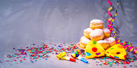 Krapfen, berliner or donuts with bow tie, streamers and confetti. Colorful carnival or birthday background