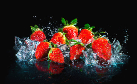 Strawberries in water splash on black background