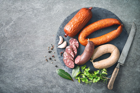 Assortment of german homemade sausage specialties: hard cured salami, liver sausage (Leberwurst), blood sausage (Blutwurst) and salami on kitchen table Stock fotó