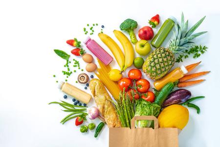 Selección de alimentos saludables. Bolsa de compras llena de verduras y frutas frescas aisladas en blanco