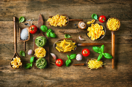 Various pasta on wooden spoons on wooden background. Top view with copy space