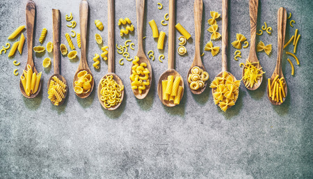 Various kinds of pasta in wooden spoons over stone background. Top view with copy space