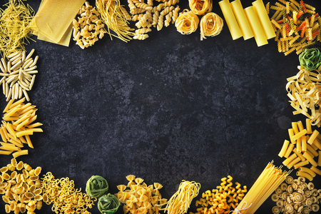 Various kinds of pasta over stone background. Top view with copy space