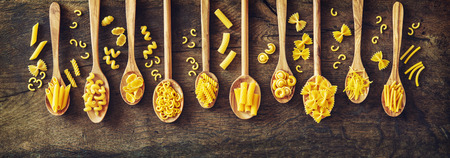 Various kinds of pasta in wooden spoons. Top view with copy space