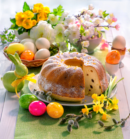 Easter yeast cake with icing on holiday table decorated with spring flower and Easter eggs, traditional Easter pastries