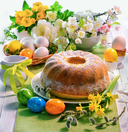 Easter yeast cake with icing on holiday table decorated with spring flower and Easter eggs, traditional Easter pastries Stok Fotoğraf