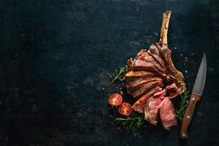 Gegrilde droge gerijpte tomahawk steak gesneden als close-up op donkere achtergrond Stockfoto