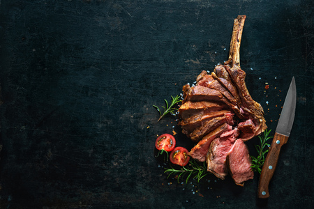 Grilled dry aged tomahawk steak sliced as close-up on dark background Banco de Imagens