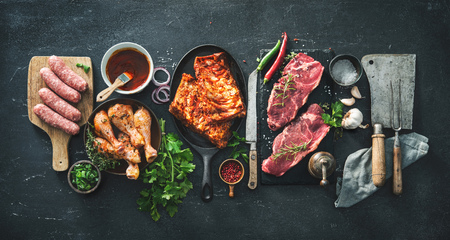 Various kinds of grill and bbq meats with vintage kitchen and butcher utensils. Chicken legs, steaks, sausages, pork ribs with herbs, spices, sauces and ingredients for grilling Фото со стока