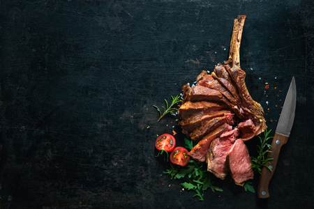 Grilled dry aged tomahawk steak sliced as close-up on dark background 免版税图像