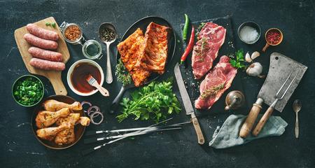Diversos tipos de carnes a la parrilla y barbacoa con utensilios de cocina y carnicería vintage. Muslos de pollo, filetes, salchichas, costillas de cerdo con hierbas, especias, salsas e ingredientes para asar