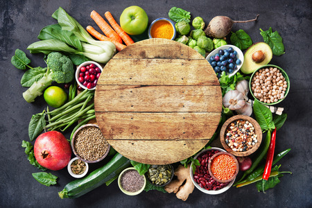 Healthy food selection with fruits, vegetables, seeds, super foods, cereals and the wooden board in the middle as copy space