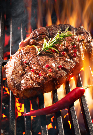 Beef steak sizzling on the grill with flames